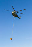 Helicopter in action. Carrying the water bucket. Shot from the ground stock photo