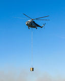 Helicopter in action carrying water bucket. Helicopter in action carrying the water bucket. Shot from the ground royalty free stock photos