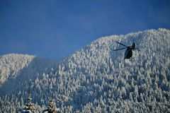 Helicopter in action on a sunny winter day. working to rescue peoples on Christmas holidays stock photo