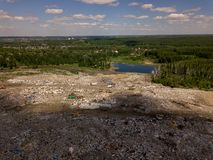 Helicopter aerial view of a big dump with a lot of garbage that pollutes nature, forest and small blue lake under the sky stock photography