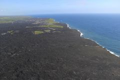 Helicopter aerial view of lava entering the ocean and steam, Big Island, Hawaii. Stock Photo