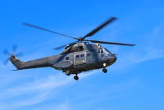 Helicopter against blue sky. Helicopter flying against blue sky Royalty Free Stock Images