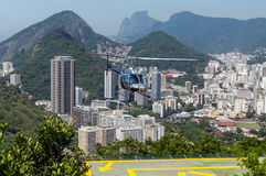 Helicopter against Rio de Janeiro, Brazil. View of Rio de Janeiro. Helipad and Helicopter in the foreground. Tours of Rio de Janeiro are given atop Sugar Loaf Royalty Free Stock Image
