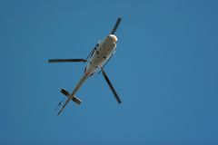Helicopter in the air. Over the blue sky Stock Photos