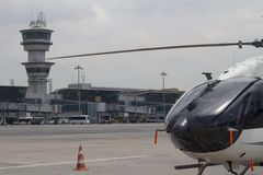 Helicopter and air traffic control tower. Close up helicopter and Istanbul Ataturk Airport air traffic control tower with background in airport apron terminal Stock Photo
