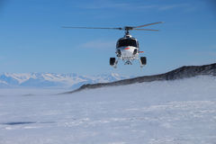 Helicopter in Antarctica. Helicopter flying in Antarctica in support of geological studies of Mount Erebus Stock Photos