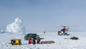 Helicopter assisted evacuation of a polar research camp. Due to cracked icefloe following storm swells Stock Image