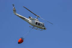 Helicopter bambi bucket fire fichting. Huey helicopter with a bambi bucket for fire fighting Royalty Free Stock Photo