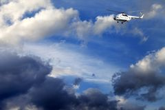 Helicopter in blue sky with clouds Royalty Free Stock Photo