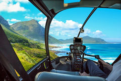 Helicopter in Cape Peninsula. Helicopter cockpit flies in Misty Cliffs, Cape Peninsula in South Africa, with pilot arm and control board inside the cabin Stock Photos