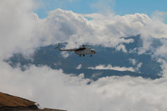 Helicopter with cargo cable and mountains in clouds Stock Photos
