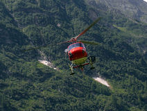 Helicopter carries cargo in the Alps Stock Image