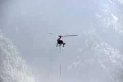 Helicopter carries cargo in the Alps Royalty Free Stock Image