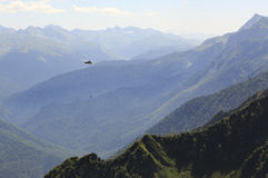 Helicopter carrying cargo in the mountains Stock Photography