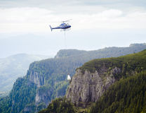 Helicopter carrying goods on mountain Royalty Free Stock Image