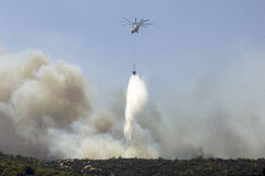Helicopter carrying water to fire. Fire fighting helicopter dropping water on forest fires in Athens Royalty Free Stock Photo