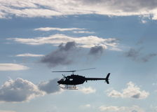 Helicopter In The Clouds. A silhouette of a helicopter flies against a cloudy sky Stock Photo