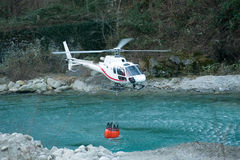 Helicopter collecting water in a bucket Royalty Free Stock Photos