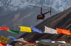 Helicopter and colorful tibetan prayer flags in Annapurna Base Camp, Himalayas stock photo