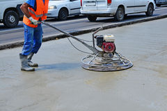 Helicopter concrete finishing. Construction worker finishing concrete with power trowel machine Royalty Free Stock Image