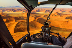 Helicopter in Dead Valley. Helicopter cockpit flies in Dead Valley, Sossusvlei desert in Namib Naukluft National Park, Namibia, with pilot arm and control board Stock Image