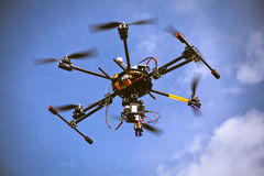 Helicopter drone filming video. Flying helicopter drone is filming video in the blue sky Stock Photography