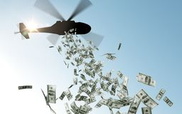 Helicopter dropping money in sky. Finance, economy and monetary policy concept - helicopter dropping money in sky royalty free stock image