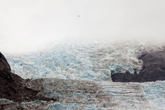 Helicopter dwarfed by nassive glacier ice flow Royalty Free Stock Images