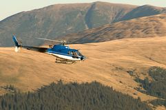 Helicopter Ecureuil AS350 B3 in flight. Rent a helicopter Eurocopter Ecureuil AS350 B3 Royalty Free Stock Images