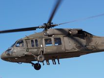 Helicopter with feet. Military Blackhawk helicopter loaded with paratroopers making a jump Royalty Free Stock Photos