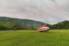 Helicopter on field in the mountains. Helicopter in the mountains on the field in the summer in a thunderstorm Royalty Free Stock Photos