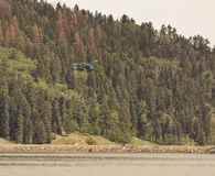 Helicopter filling helibucket. Helicopter fills a helibucket at a lake whilst fighting a forest fire in the Rocky Mountains, Colorado Stock Photo