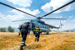 Helicopter and firefighters. Firefighters walking Stock Photo