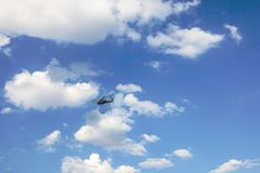 Helicopter flies in the blue sky with clouds stock photography