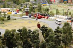 Helicopter flies and extinguishes the fire toy model royalty free stock image