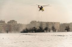 Helicopter flies with the load on the rope over snowy field Royalty Free Stock Image