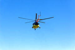 A helicopter flies off in the sky Stock Photos