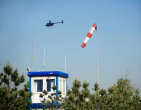 Helicopter flies over an airfield weather station in summer day Royalty Free Stock Photo