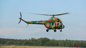 Helicopter flies over a field near the forest, helicopter games. Helicopter takes off, goes down, extreme games in the helicopter near the forest, a helicopter stock video