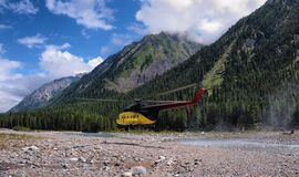 The helicopter flies over a mountain river Royalty Free Stock Photo