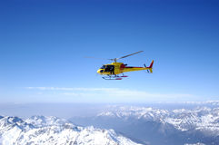 Helicopter flight. Over the snow-capped Dolomites and blue sky Stock Photos