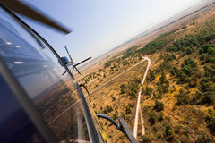 Helicopter in flight. Birds-eye view of grasslands with helicopter in flight Stock Photos