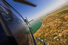 Helicopter in flight. Birds-eye view of grasslands with helicopter in flight Royalty Free Stock Image