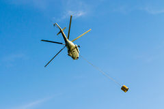 Helicopter in flight carrying bucket. Helicopter in action carrying the water bucket. Shot from the ground stock image