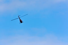 Helicopter in flight. Helicopter flying through blue skies with soft clouds Royalty Free Stock Photos
