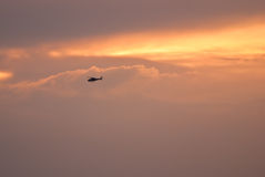 Helicopter Flying Across a Sunset Sky Royalty Free Stock Images