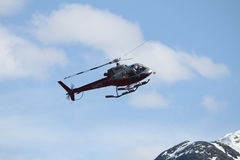 Helicopter. Flying around mountains coming in for a landing royalty free stock image