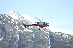 Helicopter. Flying around mountains coming in for a landing Stock Photography