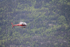 Helicopter. Flying around mountains coming in for a landing stock image