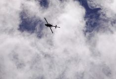 A helicopter flying in the blue sky Stock Images